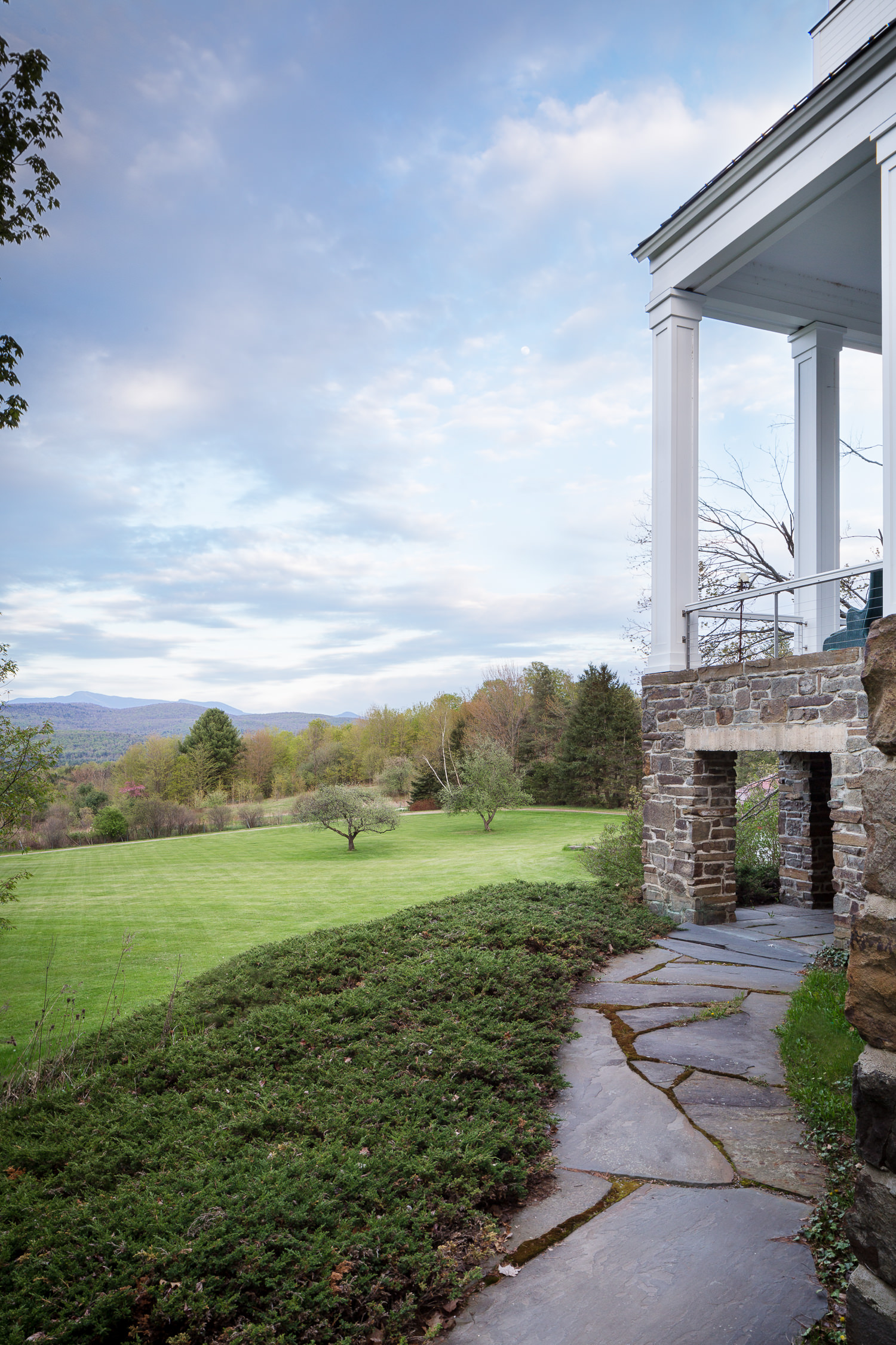 A winding stone walkway and the backyard view at the Woods Hollow vacation rental in Westford VT taken during an architecture photography session by Vermont commercial photographer Stina Booth of Studio SB.