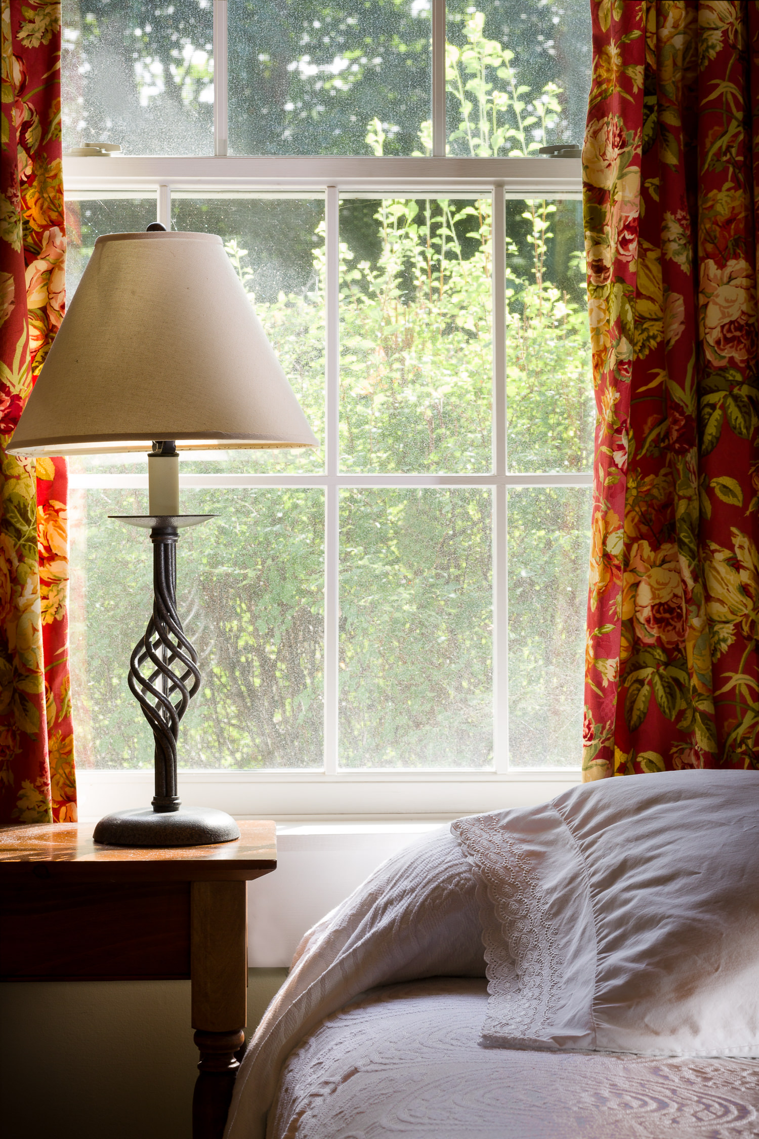 A bedside lamp detail in a Tyler Place Resort cottage bedroom for website marketing photos by Studio SB.