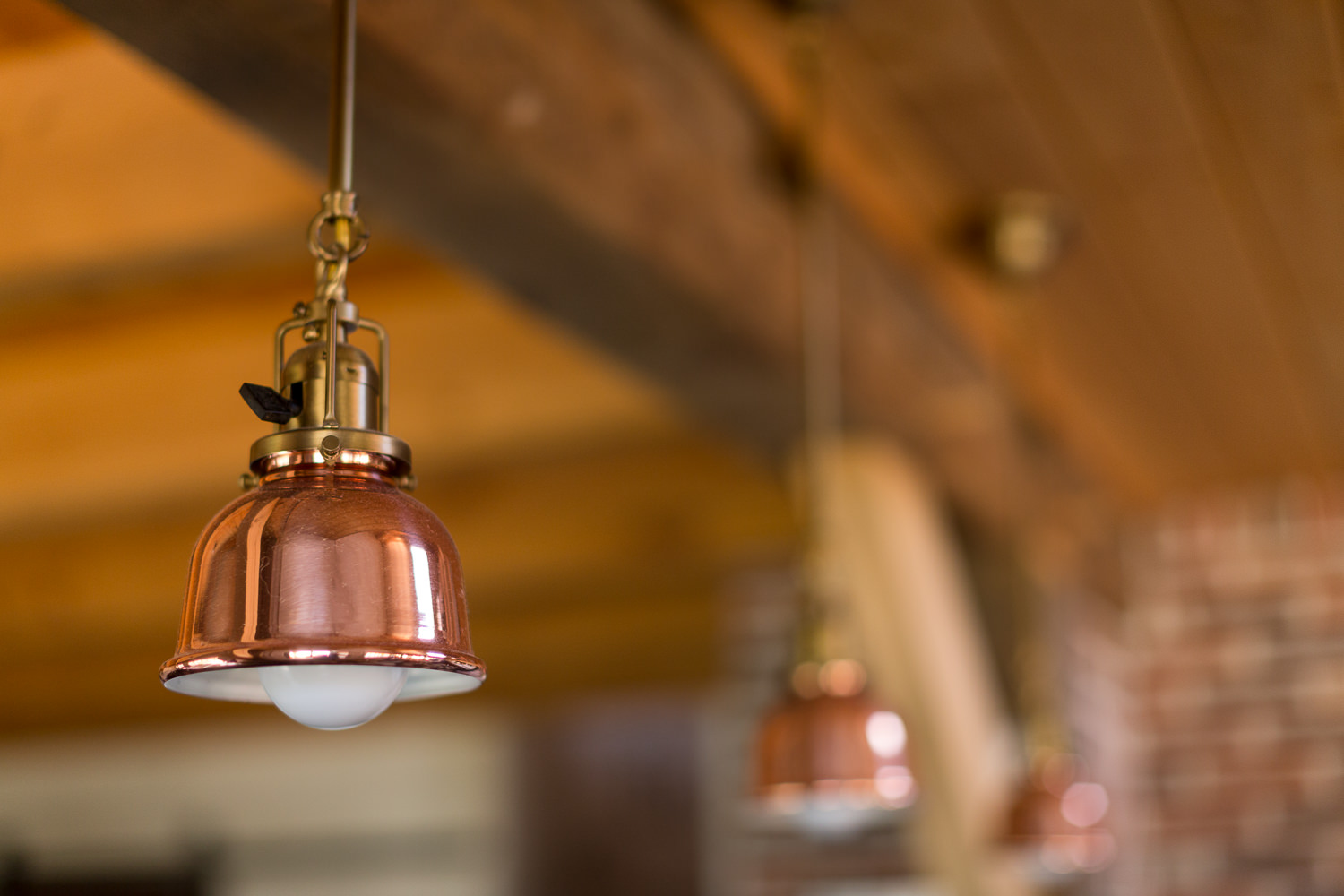 Interior architecture photo of copper lighting in efficient farmhouse built by New Frameworks Natural Building in Middlesex Vermont